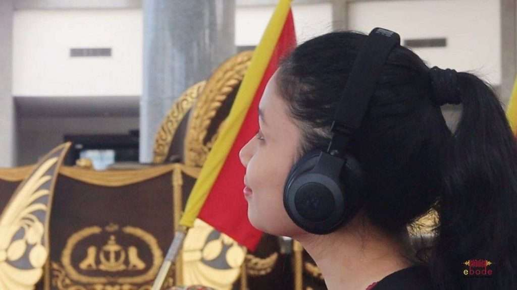 Girl listening to audio guide at Royal Regalia Museum